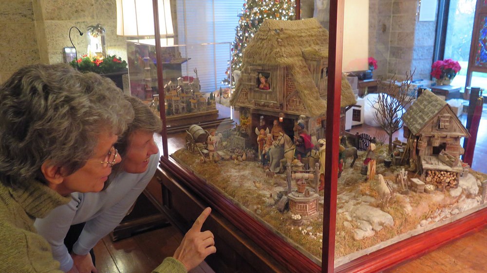 Figure 1: Artist Karen Loccisano (left) and Kirsten Hansen Gyllenhaal, one of the co-curators of the  World Nativities  exhibition, discuss the Flemish Nativity, made by Karen and her husband, Michael Palan. Photo by R. Michael Palan.