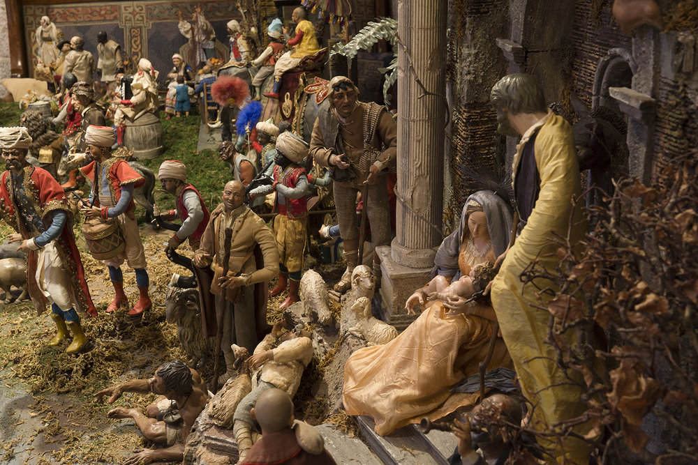 "Figure 10: The 100+ figures in this large 19th- and 20th-century Presepio were collected in Italy over a period of more than thirty years by the late Elizabeth Anne Evans of Bucks County, Pennsylvania. A Presepio, which has been called ""the translation of the Bible into Neapolitan dialect,"" represents daily life in 18th-century Naples, a bustling port city. The miracle of the Nativity is depicted as taking place amid crumbling Roman ruins, signifying the end of paganism and the dawn of Christianity. On loan from the Fleisher Art Memorial, Philadelphia, Pennsylvania."