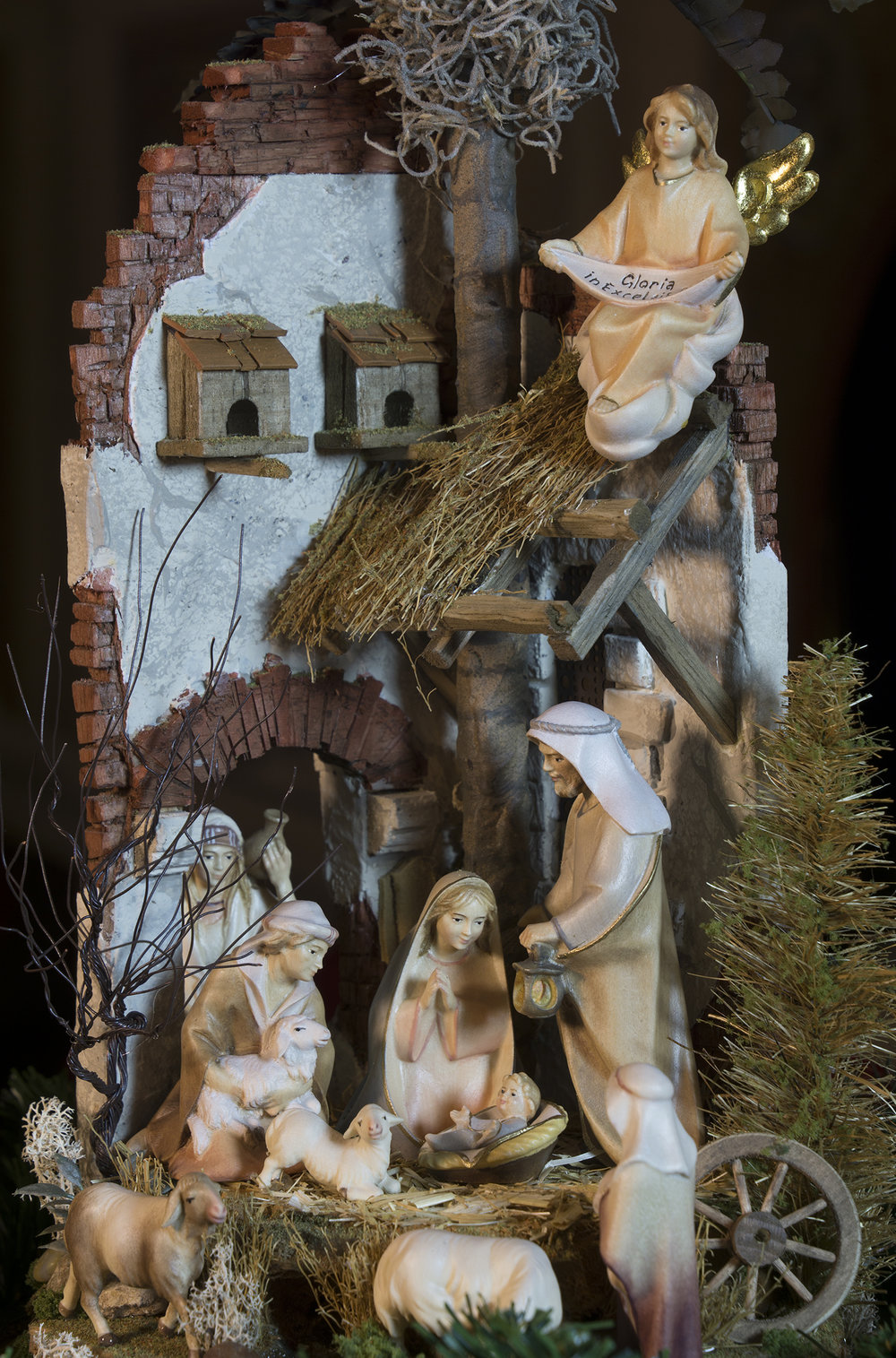 "Figure 12: This presentation of a Nativity ""in the round,"" nestled inside an antique French cloche (a glass covering for garden plants to prevent frost damage), features many finely crafted details, including handmade trees, crumbling ancient bricks, dove houses above the roof, and a small stream. The setting was created by  Navidad Nativities  of Bucks County, Pennsylvania, and the figures were carved from mountain maple and painted in the studios of Ulrich Perathoner at Val Gardena in the Italian Alps. On loan from Navidad Nativities, Bucks County, Pennsylvania."