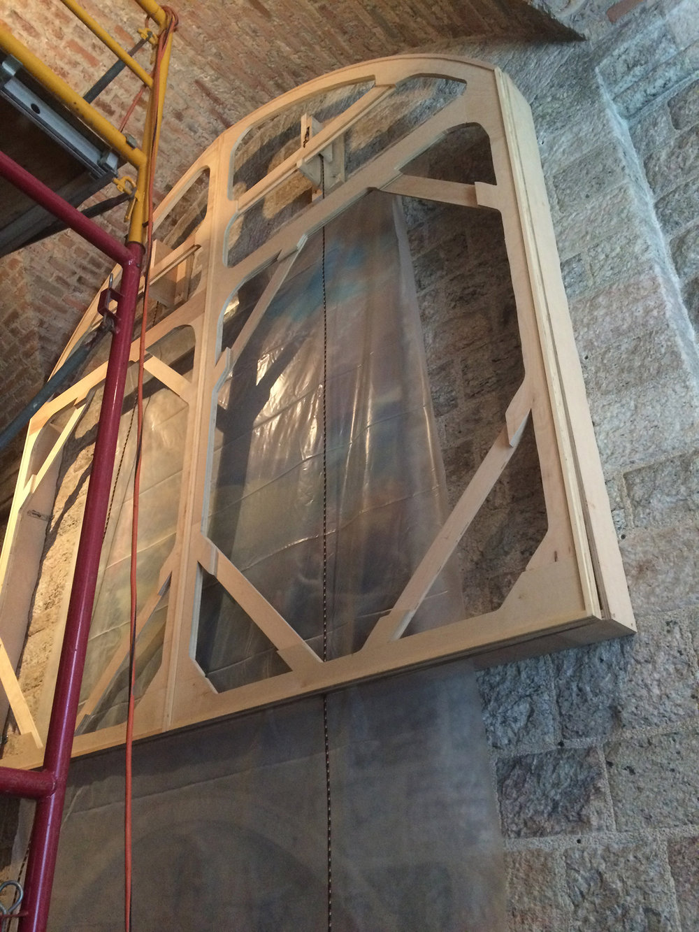 "Figure 13: ""This is a dry run, hanging the frame built by Lewis Grubb before the the canvas was stretched over it. The painting that hangs over the fireplace for the rest of the year can be seen under the plastic sheet. The dry run proved to be very successful—everything worked as planned!"" (Edwin Herder)"