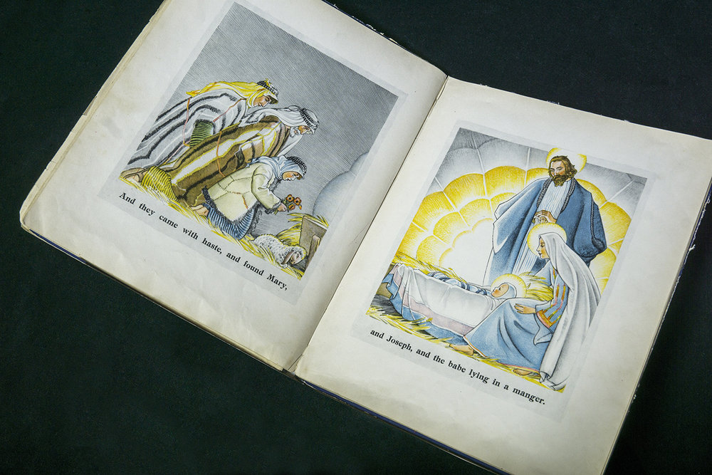 "Figure 1: A first edition (1931) of  The Christ Child , opened to a two-page spread with the Adoration of the Shepherds. ""Here is a picture book that in its reverent and childlike beauty has captured the very spirit of Christmas. Before making the pictures Maud and Miska Petersham went to Palestine, with the result that the characters of the Christmas story move across a background both beautiful and authentic"" ( The New York Times , December 13, 1931, p. 12)."