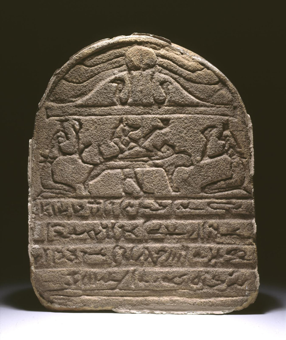 Figure 7:  Anubis . This god is often shown attending to the mummified deceased. Individuals may have wanted amulets of Anubis to offer protection to their mummified remains (see Figure 6). A funerary stela from the site of Dendereh shows Anubis attending to the mummy of the deceased; Isis and Nephthys flank either side of the funerary bier. Image courtesy of Penn Museum, E2983.