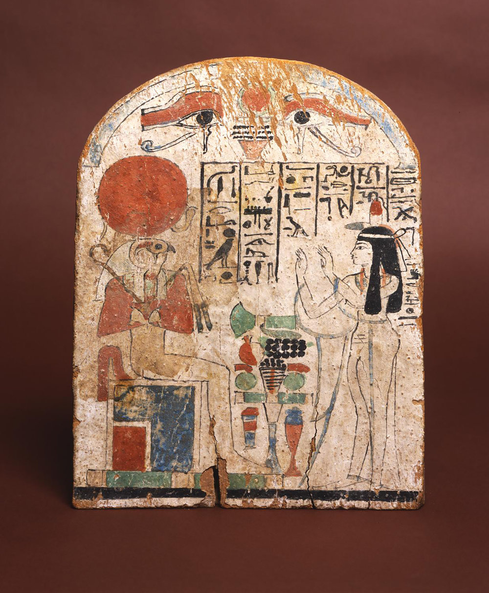 Figure 12:  Re-Horakhty . Tasheryt, the Chantress of Amun, worships the god Re-Horakhty (see Figure 11) on this painted wooden stela. The god is identified by name in the hieroglyphic inscription. Image courtesy of Penn Museum, E2043.