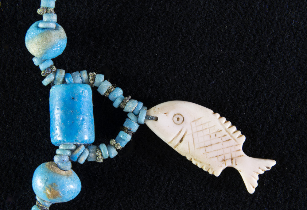 Figure 21:  Fish .   Glencairn necklace 15.JW.43 features an amulet of a fish. Given the importance of the Nile River, it is not surprising that fish imagery is found in amulets. One type of fish, the tilapia, was a symbol of rebirth and regeneration. Fish amulets may also have been worn to protect one from drowning. Glencairn Museum 15.JW.431.