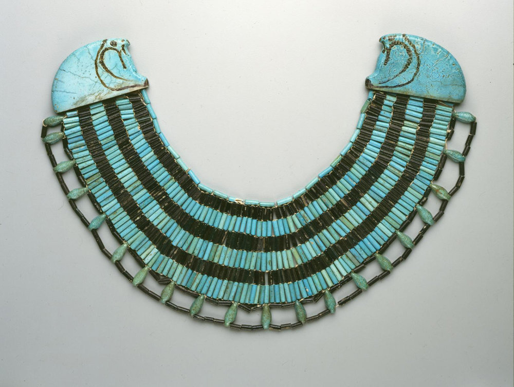 Figure 38: Excavated at the site of Meydum, this beautiful broad collar ( wesekh ) is made of blue and black faience. Each end of the collar is decorated with a terminal in the shape of a falcon head. Both men and women wore necklaces like this in ancient Egypt. Image courtesy of Penn Museum, UPMAA 31-27-303.