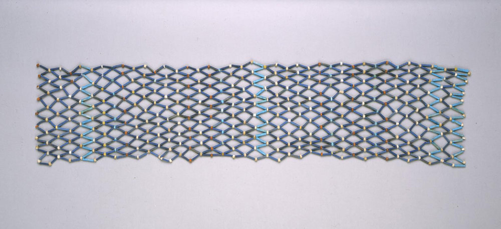 "Figure 39: Some mummies were covered with shrouds made of beaded netting. These tubular beads are made of faience and are often referred to as ""mummy beads."" Image courtesy of Penn Museum, UPMAA E2179."