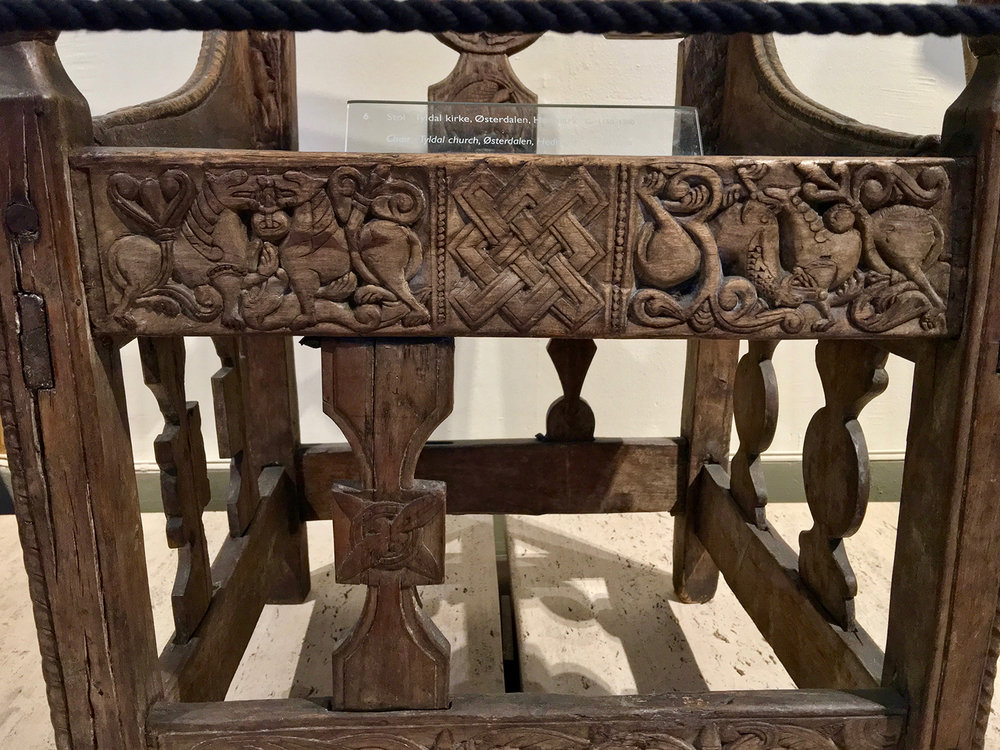 Figure 4: A detail of the front of the original Tyldal chair, photographed in the Medieval Exhibition Room (middelalderutstillingen) at Kulturhistorisk Museum, Oslo, Norway. The design at the center of the front vertical spindle (the right one is missing) was copied in the Glencairn chair. Photo © User: Wolfmann / Wikimedia Commons.