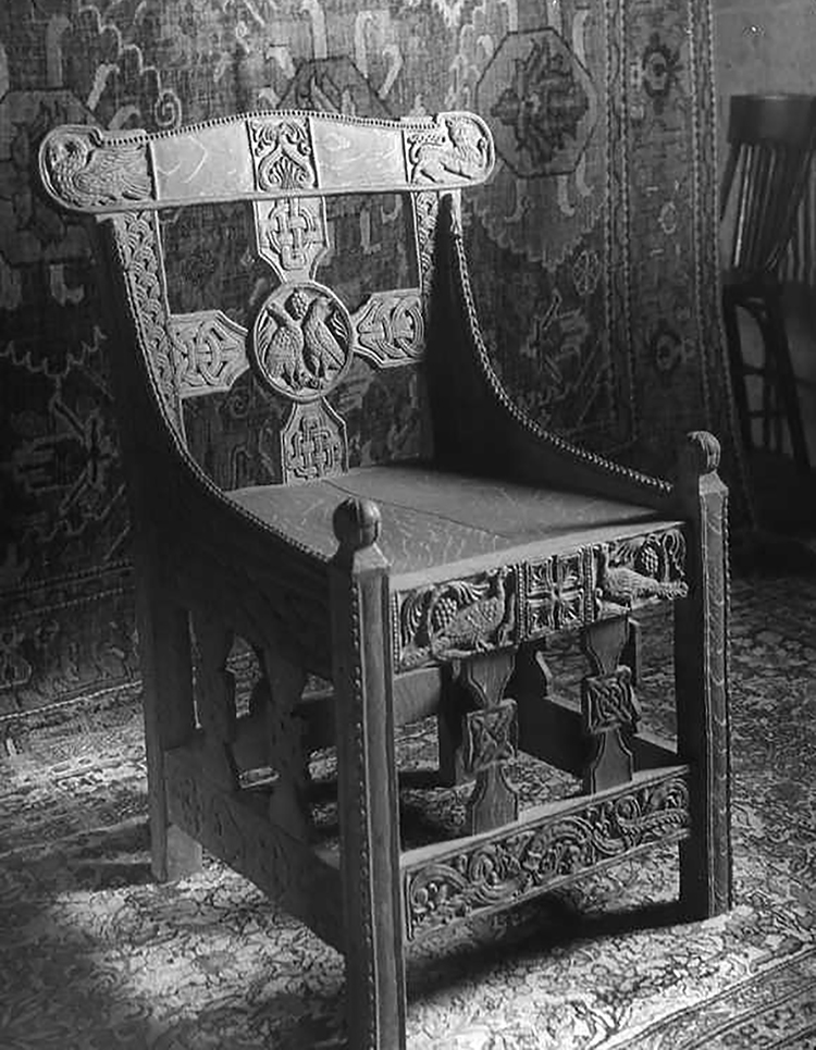 "Figure 20: At some point after it was carved, Glencairn's ""Tyldal chair"" was photographed in the Bryn Athyn Cathedral woodworking shop with an oriental rug as a backdrop. Several of the Cathedral's chairs were photographed as well. This archival photograph (#3875) comes from a collection of glass negatives in the Glencairn Museum Archives."