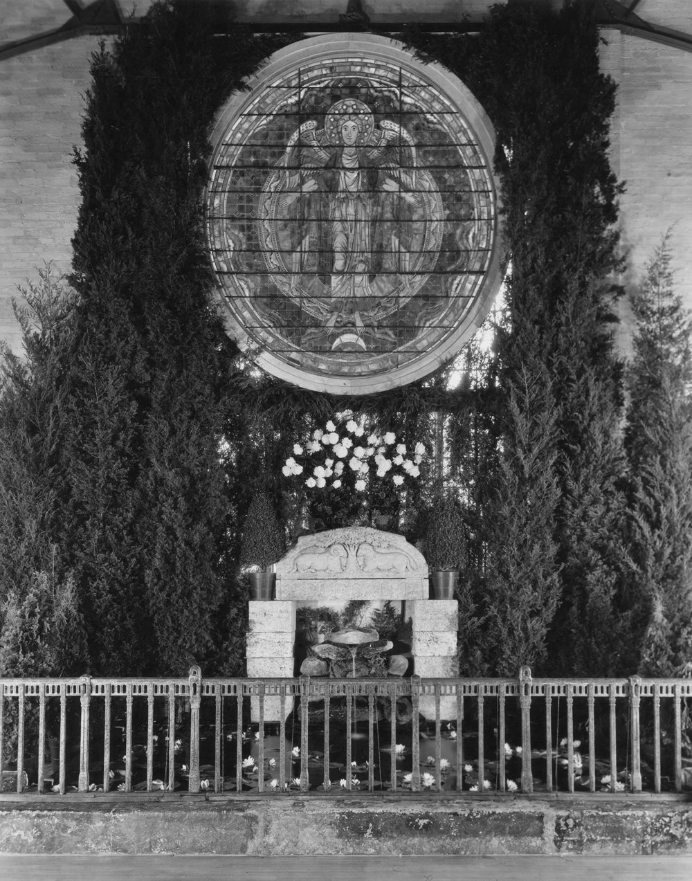 Figure 17: The end of the Assembly Hall, opposite the stage. Decorations included a stained glass window depicting the Woman Clothed with the Sun, a Monel metal railing, and the lintel of Glencairn's front door.