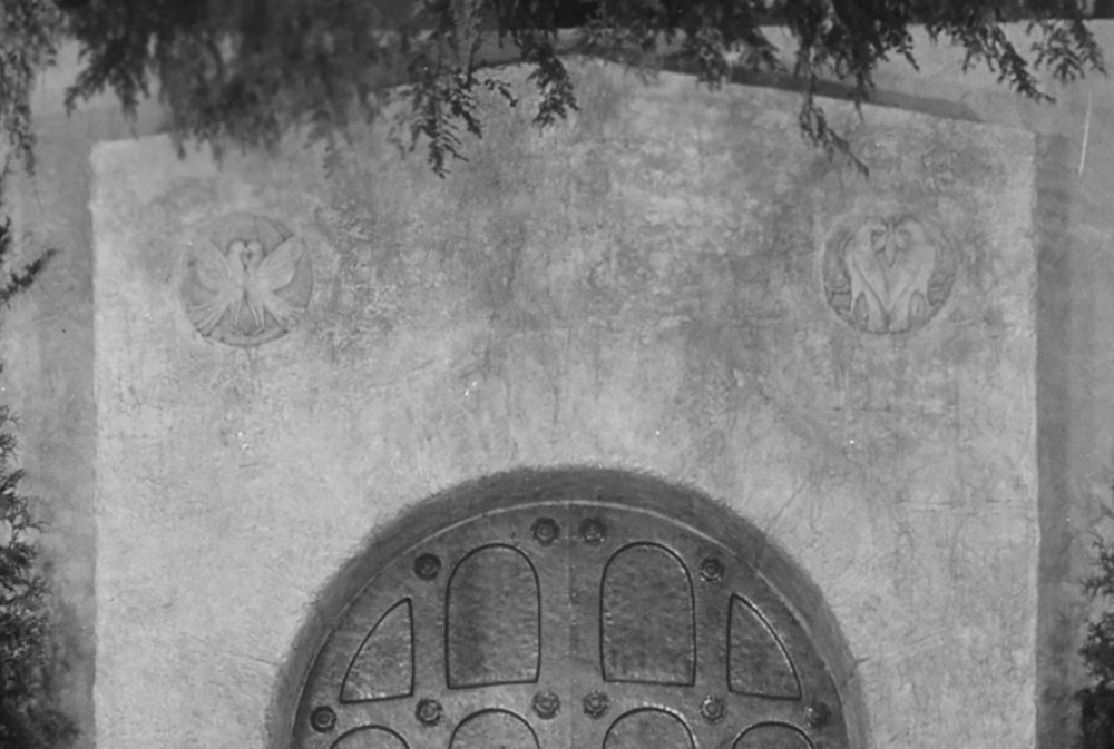 Figure 9: Two plaster medallions with doves can be seen above the bronze door on the Assembly Hall stage. They were never realized as finished designs in Glencairn.