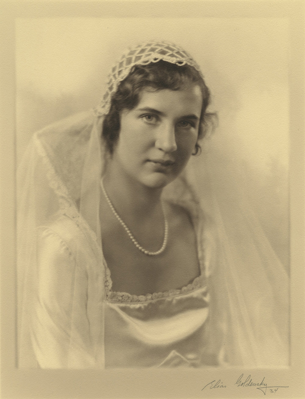 "Figure 2: Gabriele Pitcairn posing for one of her formal wedding portraits. ""The bride was attired in a white satin gown with lace stand-up collar and train, and wore a cap of rhinestone crossed bands"" (""Church News,""  New Church Life  1934, p. 296). Photograph by Elias Goldensky."