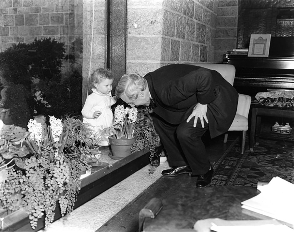 Figure 1: Raymond Pitcairn smells a hyacinth, while one of his granddaughters looks on, circa early 1960s.