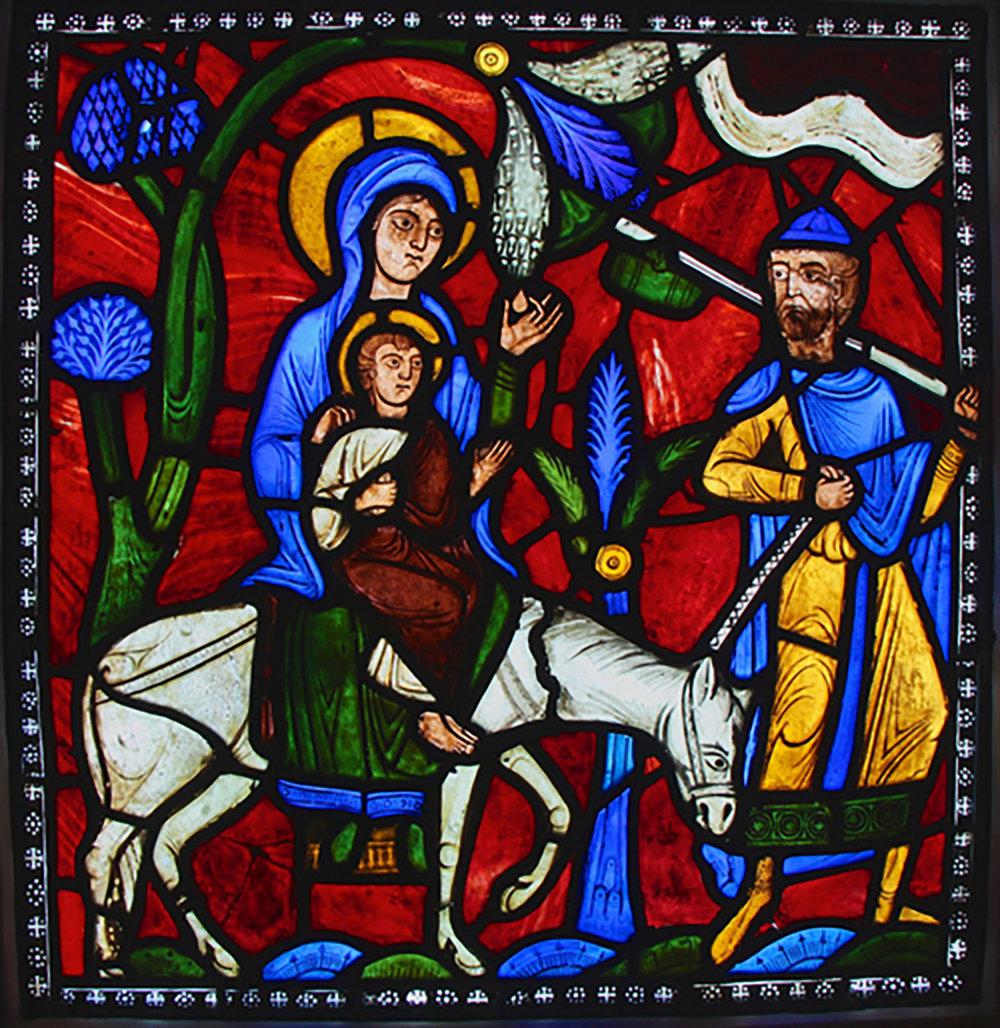 The Pitcairn Flight into Egypt, from the Infancy of Christ window of the Abbey Church of Saint-Denis, France, c. 1140-1145 (Glencairn Museum, 03.SG.114). This is an unusually well-preserved panel of medieval stained glass. The only significant modern restorations are the white strip of ornament that surrounds the panel as a frame, and the white tether that runs between Joseph's hand and the donkey's head.