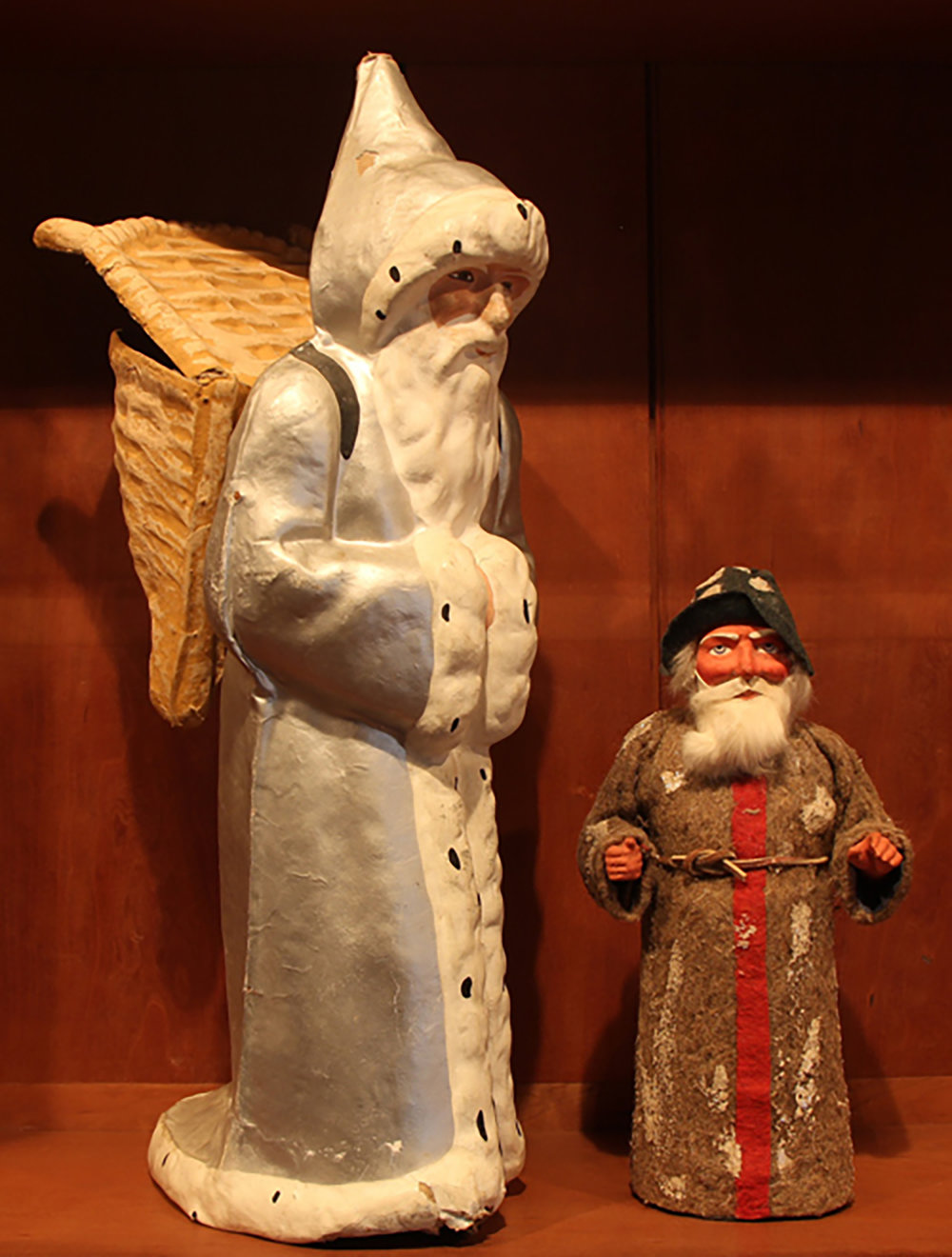 Figure 5: Left: Père Noël is the French equivalent of the American Santa Claus. He wears a long, hooded robe edged with white fur, and carries presents in a wicker basket like the ones traditionally used by grape harvesters. This papier-mâché figure of Père Noël, made in France around 1920, served as a candy container. Right: This St. Nicholas-shaped candy container, made in Germany around 1910, separates at the base and conceals a cylinder that held candy.