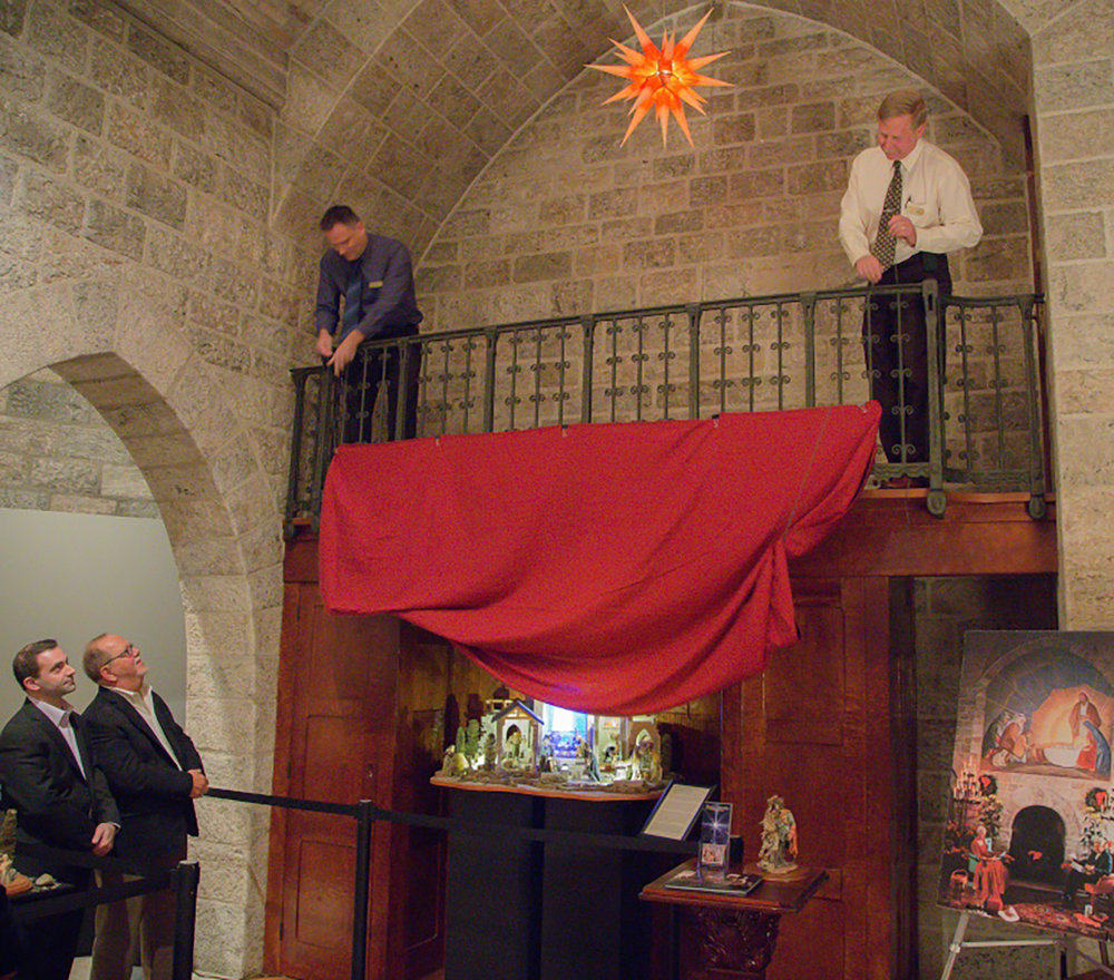 Figure 11: A.J. DiAntonio (far left) and Michael Stumpf witness the unveiling of  The Glencairn Nativity  at an exhibition preview on November 23, 2015. Photo: Kyle Genzlinger.