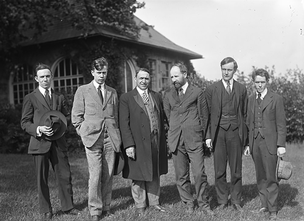 Figure 6: From left to right, Rowley Murphy, Paul Froelich, John Larson, Lawrence B. Saint, Raymond Pitcairn, and Winfred S. Hyatt stand in front of Cairnwood's garden house, which was used as a stained glass studio. Murphy, Froelich, Saint and Hyatt were employed as stained glass artists. Larson managed the glass factory for the first few years of its operation.