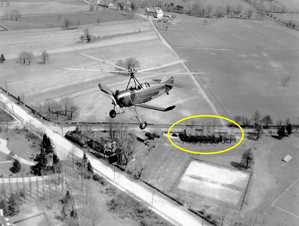 Figure 7: A Pitcairn PAA-1 Sport autogiro with one passenger flies over the Bryn Athyn glass factory (circled) and the old Academy of the New Church tennis courts. The Huntingdon Turnpike, the main thoroughfare, is clearly visible, as is the hay barn (top) for Cairnwood Farms. The glassworks made its first batch of glass on July 5, 1922, and was in continuous operation until April, 1942.