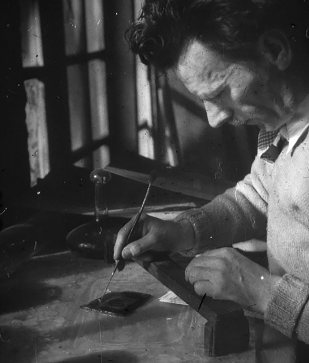 "Figure 15: Once the pieces of glass were cut, the Bryn Athyn artists carefully painted on the faces, hands, feet, and other details. The pieces were then fired in a small electric kiln, bonding the paint to the glass. In this photograph, Albert E. Cullen paints a piece of glass using a ""bridge"" to steady his hand."