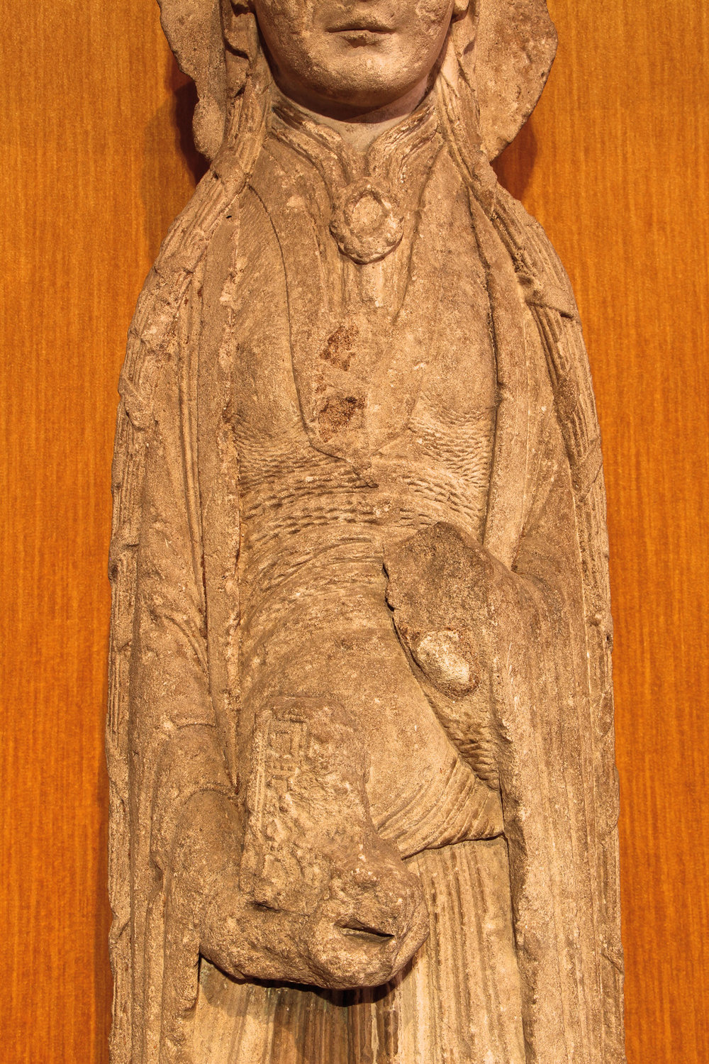 Figure 2: The woman depicted in the sculpture wears the garments of a highborn medieval lady. She holds the remains of a book in her hands.