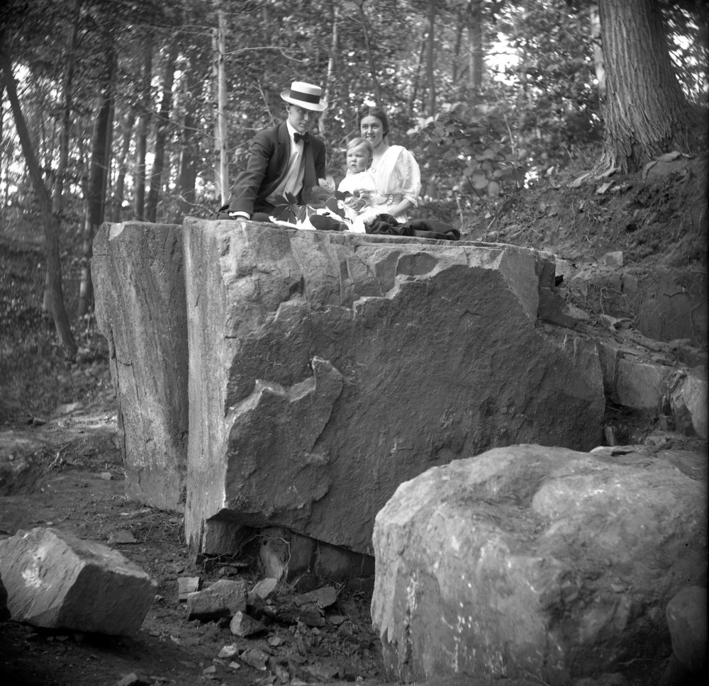 Figure 2: Raymond and Mildred Pitcairn pose on the cornerstone in the woods with their son Nathan.