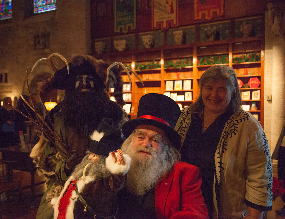 """Figure 6: Nancy Schnarr-Bruell, from Bryn Athyn, Pennsylvania, poses with """"Belsnickel"""" (aka Patrick Donmoyer, director of the Pennsylvania German Cultural Heritage Center) and """"Santa Jr."""" (aka Jim Morrison, founder/curator of the National Christmas Center). Santa Jr. is holding a Belsnickel doll crafted by Schnarr-Bruell. Photo taken in Glencairn's Great Hall in 2016."""