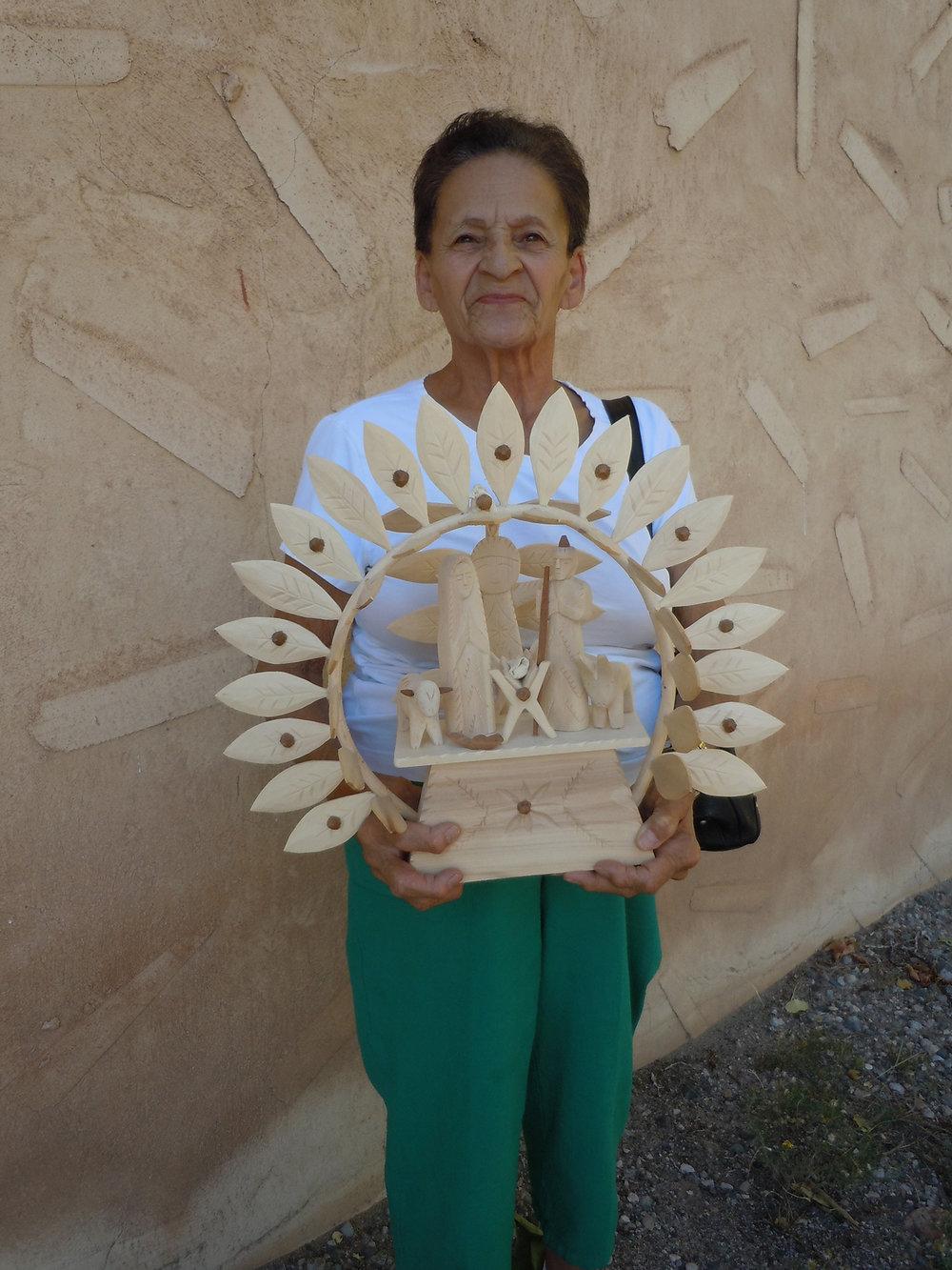 Figure 15: Sabinita López Ortiz, Córdova, New Mexico, poses with her Nativity santo pictured in Figure 14. Made in 2018. Photo courtesy of El Potrero Trading Post.