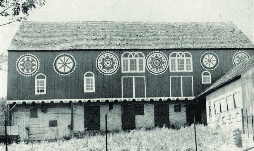 Figure 12: Historic Bucks County Barn, Photograph by Guy F. Reinert, ca. 1950, Pennsylvania German Cultural Heritage Center, Kutztown University.  This barn once stood in Bucks County, near the border with Lehigh and Montgomery, and was painted by the prolific Noah Weiss (1842-1907), a hotel proprietor, wood carver, and folk artist of the Lehigh Valley. Weiss had no formal training, but was a master carver and painter, producing religious scenes of biblical stories for the walls of his hotel. He was also an innovative designer whose elaborate barn stars featured intricate raindrop patterns in radial formations that have become classic in the Lehigh Valley.