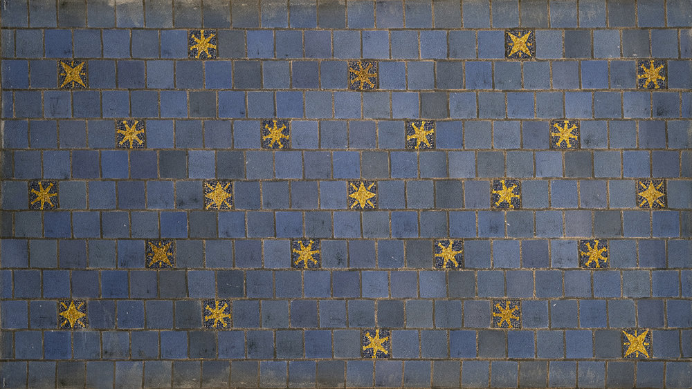 Figure 7: The recessed spaces between the ceiling beams are covered with acoustic tiles in various shades of blue, with yellow mosaic stars.