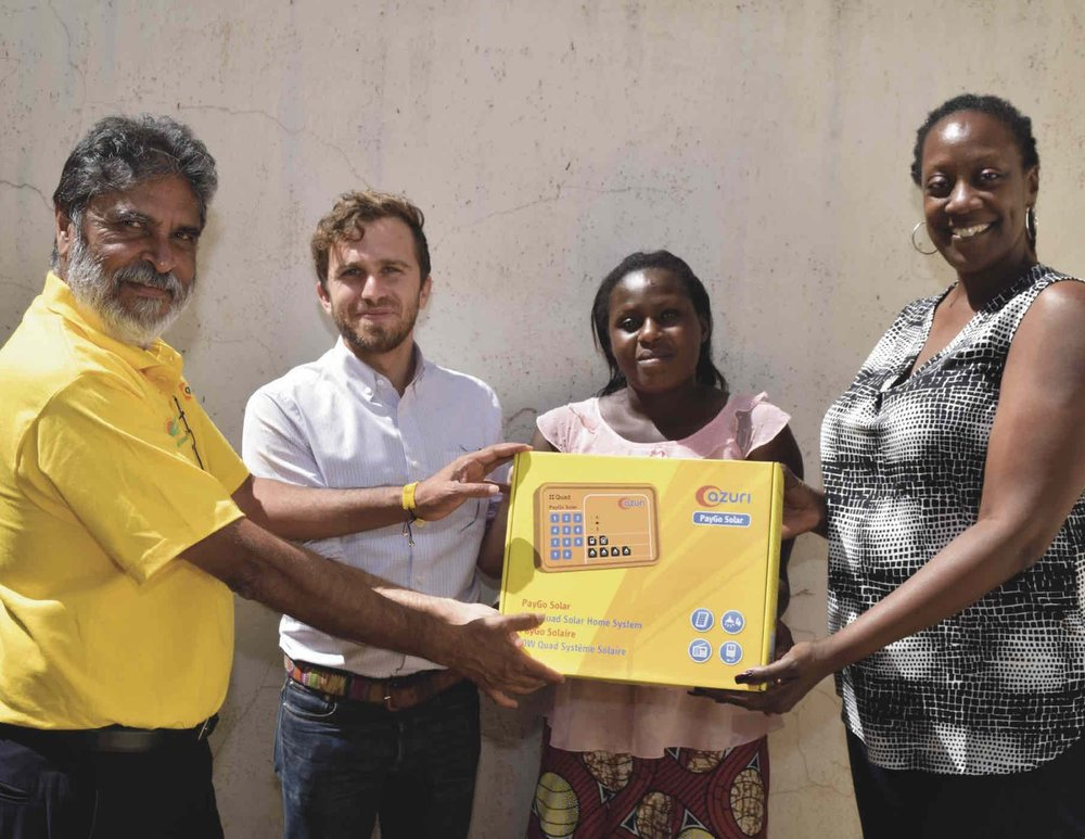 Photo: Raju Haria, CEO of Raj Ushanga House (left), Daniel Goldfarb, CEO of Lendable (second from left), and Sharon Arungu-Olende, head of East Africa for Lendable (right), provide a PAYGo solar system to a customer.