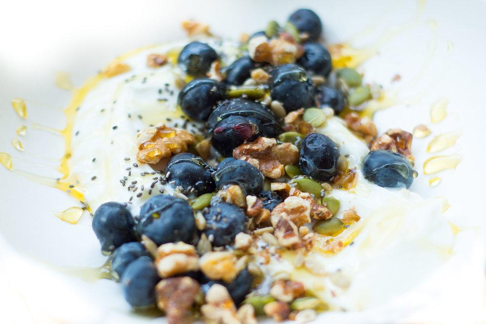 Greek yogurt bowl with fresh blueberries, local honey, and walnuts.