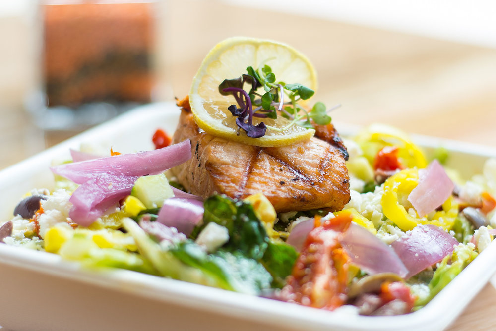 house salad with pickled onions, olives, feta, roasted tomato served with house tomato caper vinaigrette and choice of protein (salmon pictured).