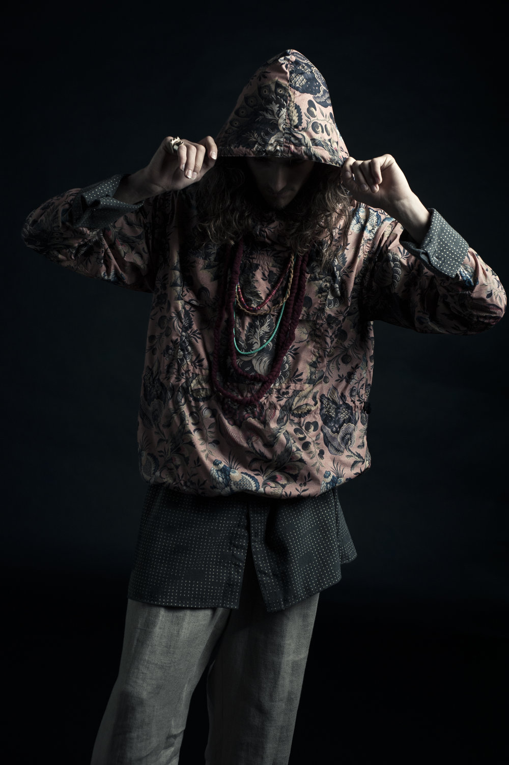 Floral windbreaker poncho, Dries Van Noten. Tunic top by Frank Tsai, MFA Fashion Design and Andrea Nieto, BFA Textile Design. Layered pants by Didvik Kuang, MFA Fashion Design. Beaded necklaces, model's own. Fabric necklaces made from UNIQLO sweaters.
