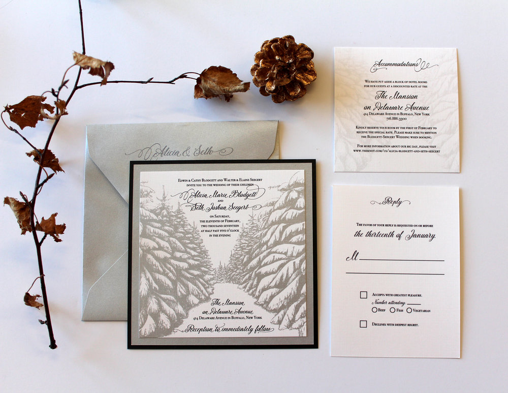 The Evergreen This suite features a quiet path through snowy pines that is perfect for a winter wedding! Especially for that couple that loves skiing, the outdoors, or just loves snow and nature. Suite pictured has digital silver printing, but is available in any color or an upgrade to a pocketfold for the Couture Suite.