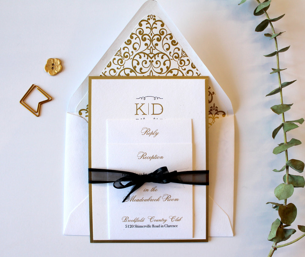 The Monogram   A simple gold foil monogram, surrounded in a gold border, paired with black letterpress. Shown here with a gold, patterned envelope liner, and digital gold enclosure cards. Suite can be customized in your colors, and is also available in one color foil or letterpress printing, printed in digital gold as part of our Standard Suite, or paired with a pocketfold for our Couture Suite.