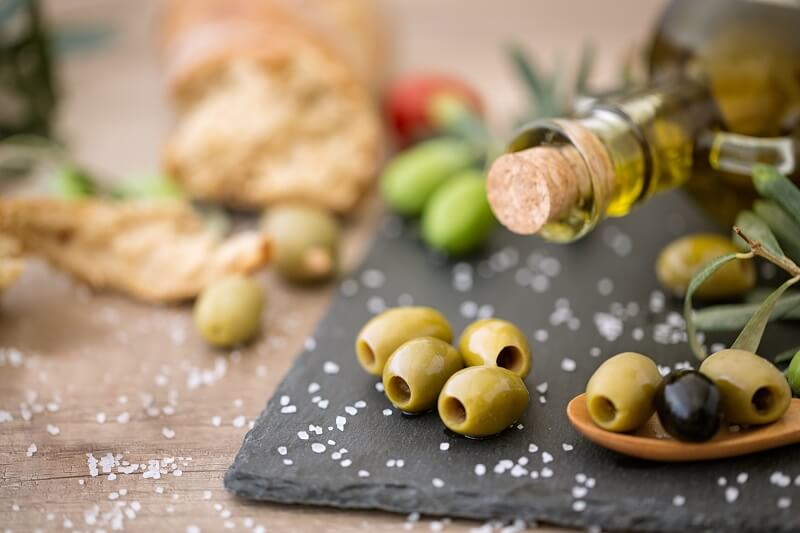 olives and olive oil on a wooden table .