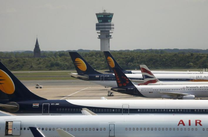 The traffic control tower is seen in the background past a row of aircrafts on the tarmac at Zaventem international airport near Brussels, Belgium, May 27, 2015.
