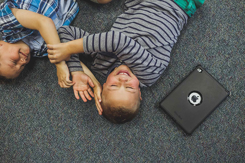Photo of Boys on Carpet Next to iPad Taken by the Camarillo Commercial Photographer at Harper Point.