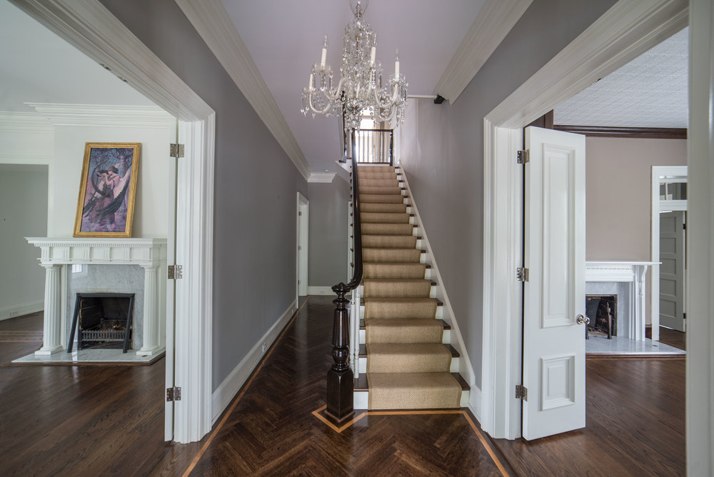The entry way featuring herringbone hardwood floors flanked on either side by expansive parlors.