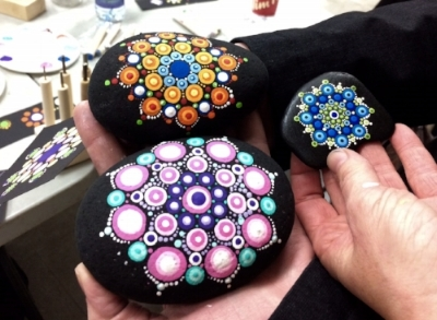 One workshop is all you need to get dotting! The two larger stones in this picture were painted by a workshop participant. The smaller mandala is a Travelling Kindness Rock. Your participation will help send more on their journeys.