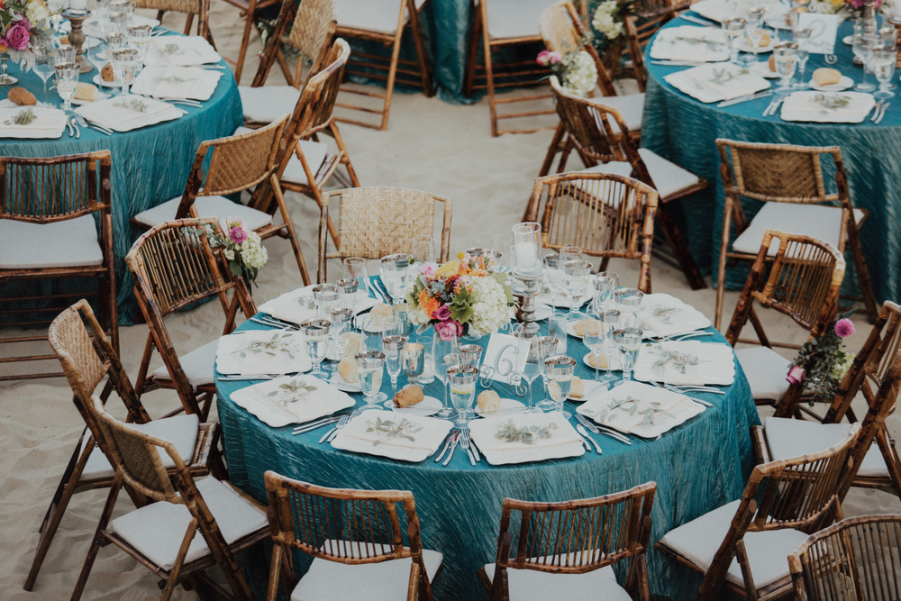 Felici Events Wedding Table Seating Wooden Chairs Blue Linen White Plates Silverware Glassware Flowers Sand