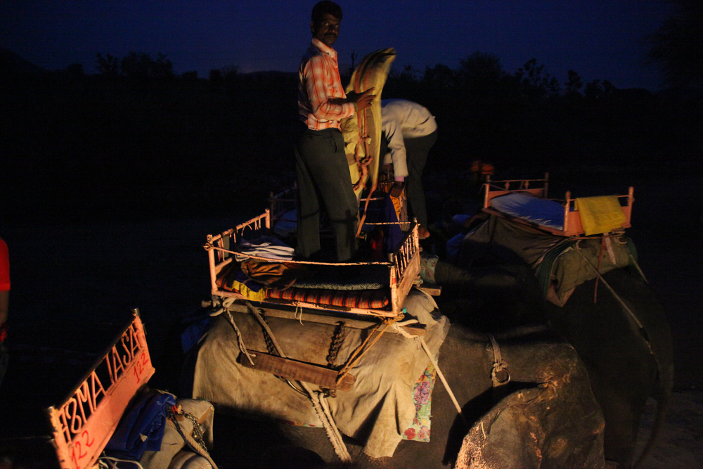 As night falls, elephant trainers pack up for the day to let the animals rest.