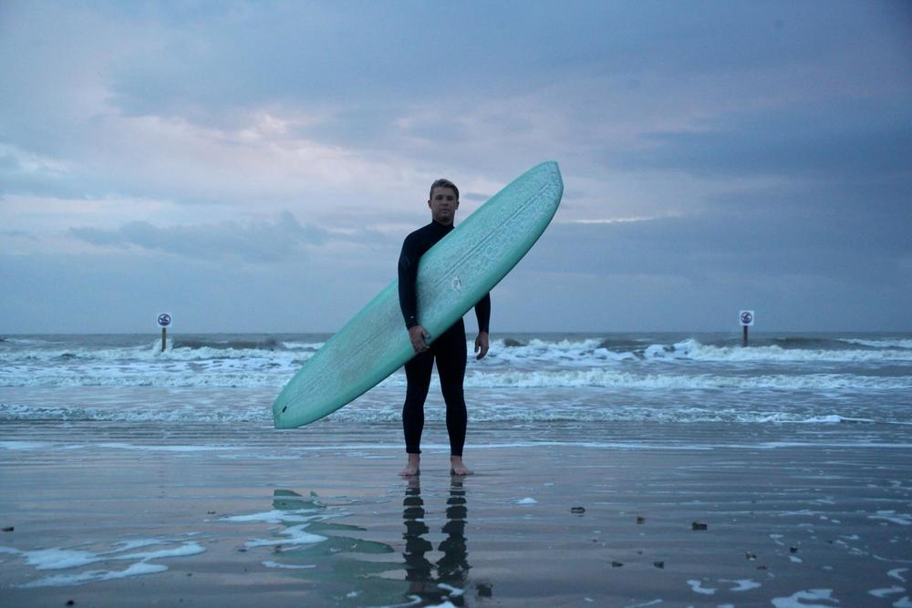 Connor stands after a surf session at 37th street on Galveston Island, Texas. The barrier island receives occasional surf from disorganized wind chop.