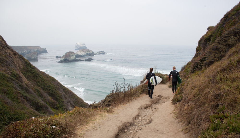 Connor Eck and Tasha Rivard hike the trail down to surf Sand Dollar Beach in Big Sur, California.