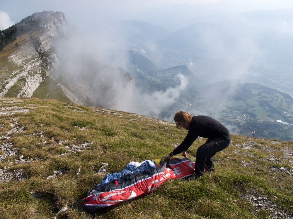 Tash laying out her glider in preparation to launch from Dent du Crolle