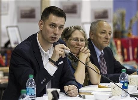 Justin Buller, left, Associate Deputy General Council, Dept. of Army, Office of General Counsel, answers questions about the repatriation process. Courtesy of  AP