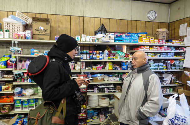 Inupiaq photograher, Brian Adams, interviews a man at the grocery store. Photo from:  KTOO Public Media