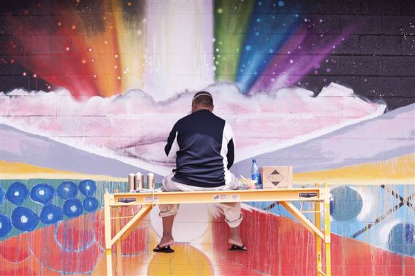 "John ""Prime"" Hina, one of the artists featured in ""Mele Murals,"" painting a community mural in Waimea, Hawaii.     Photo credit: Evan Loney/NBC News"