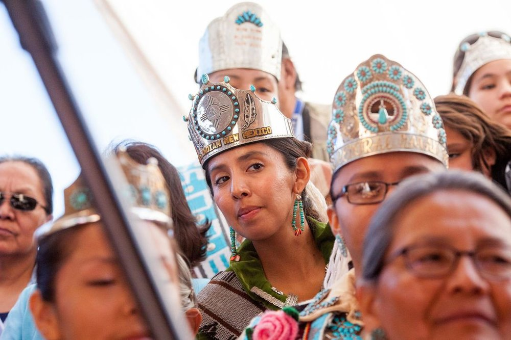 Audience members in the VIP section at the Miss Navajo Nation in 2015, including Miss Indian New Mexico Nicole Johnny, 25, center, look on during the butchering competition. (Allison Shelley)