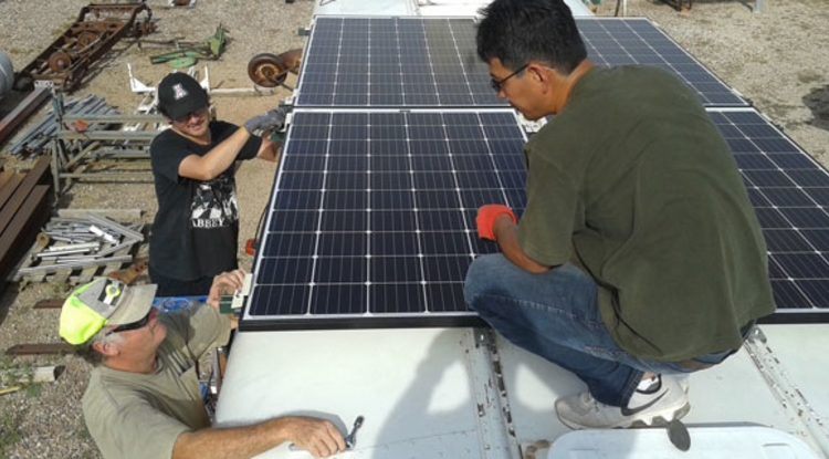 Members of the UA-AATech team mount solar panels on the roof of the desalination bus made for the Navajo Nation by UA engineers. lutheran indian ministries news