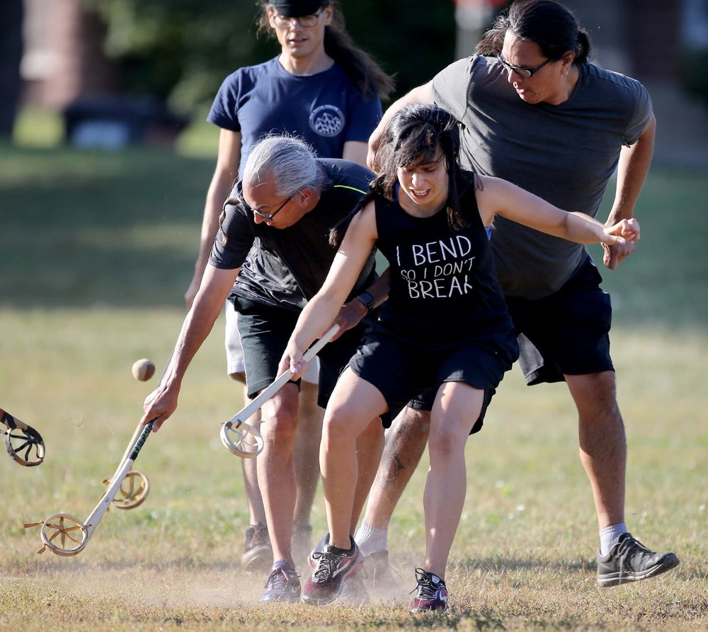 Sasha Houston Brown, center, battled for the ball during an evening of the Creator's game, which closely resembles lacrosse, in a Minneapolis park. — David Joles, Star Tribune